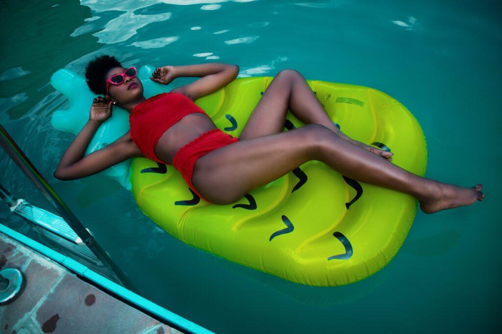 Black woman in red bikini riding a green pool float